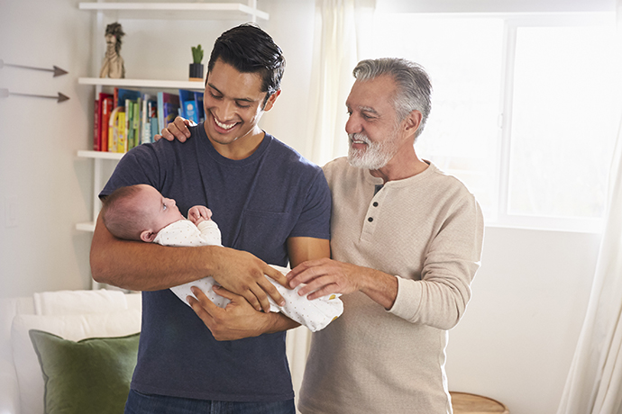 Proud senior Hispanic man standing with his adult son holding his four month old boy